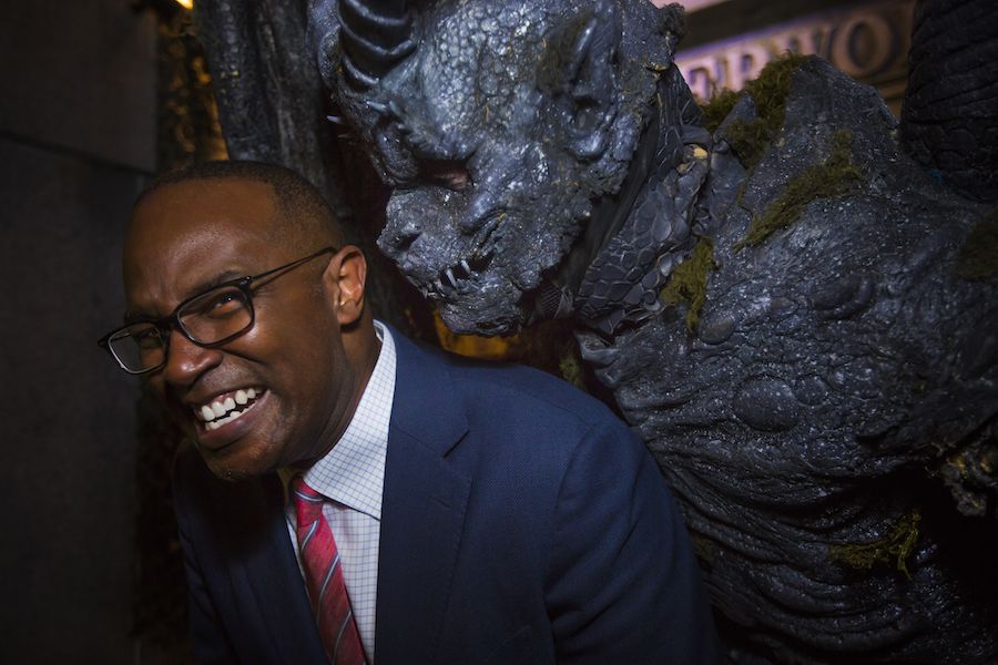 Carter grimaces and laughs while a costumed monster leans over his shoulder