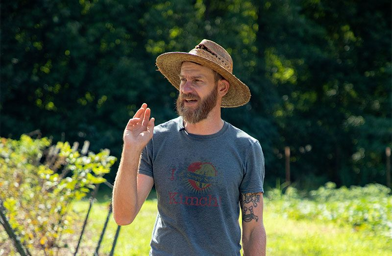 Wearing a straw hat and t-shirt, Joe Reynolds stands in one of the fields he farms.