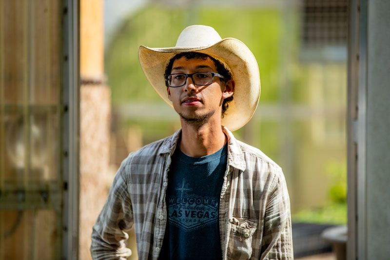 Demetrius Milling, wearing a cowboy hat and plaid shirt, photographed on the farm where he works
