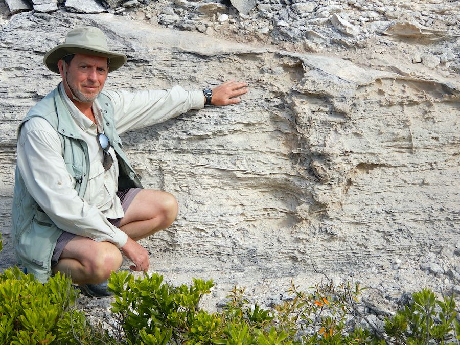 man squats and points to disturbance in layers of rock