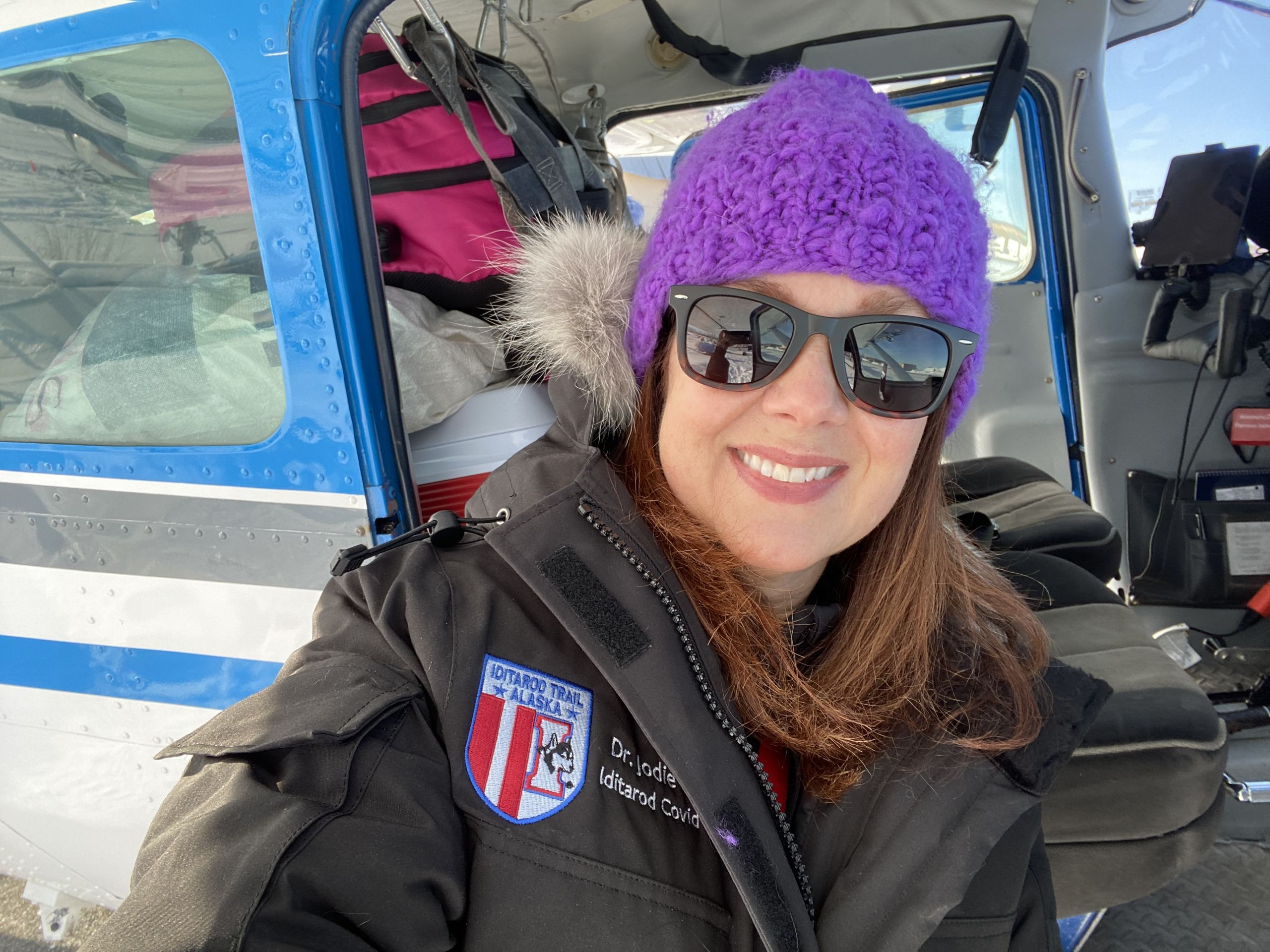 Jodie Guest poses by the door of a small airplane. She is wearing a winter hat, sunglasses and a winter coat with a patch with the Iditarod logo