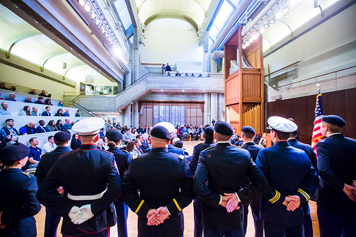 In a view from behind, a group of military service members stand at ease in the Cannon Chapel