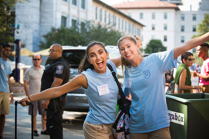 Two enthusiastic volunteers greet new students.