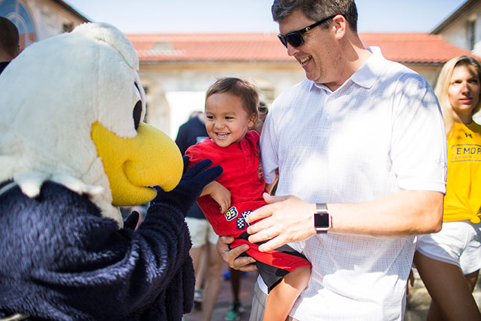 Emory's official mascot, Swoop, greets a new student's family members.