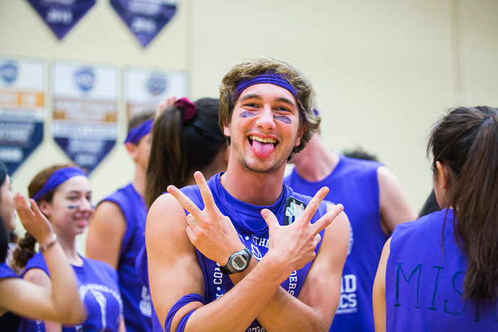 An Oxford College student wearing purple face paint poses for the camera.