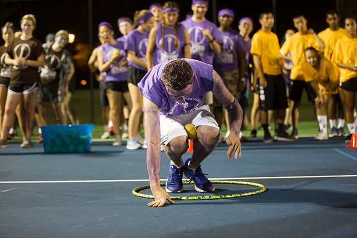 An Oxford College student wearing purple and yellow for his team stands in a hula hoop.