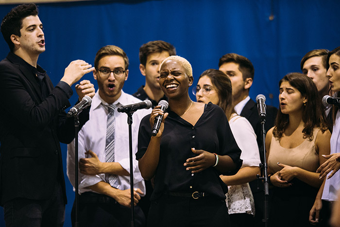 A choral group performs on the stage.