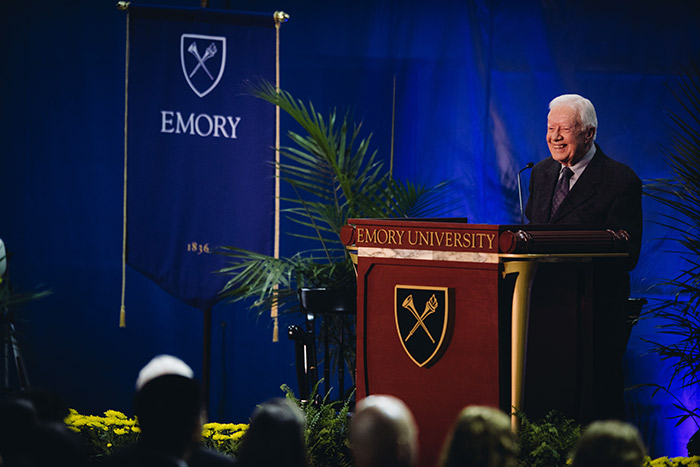 President Jimmy Carter stands smiling at the podium.