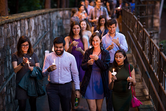 Students cross the Emory bridge holding candles over Houston Mill Road to the Miller-Ward Alumni House.