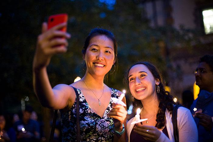 Students take a selfie as they cross the Emory bridge.