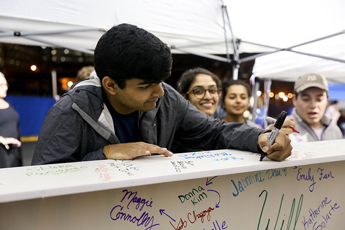 A student adds his name to the top of the beam in black marker.