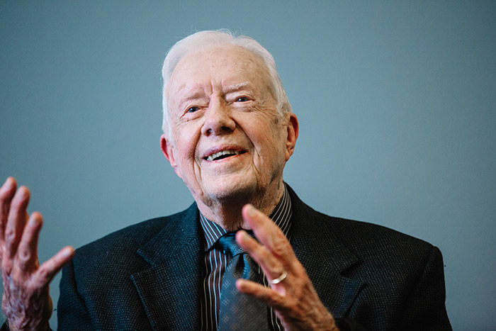 President Jimmy Carter smiles and talks with his hands to a class of eager students.