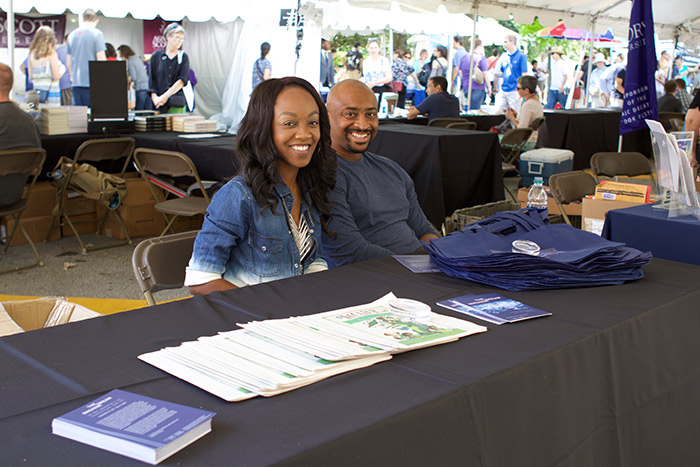Two people sit at the Emory tent, ready to offer free totes and information to festival participants.