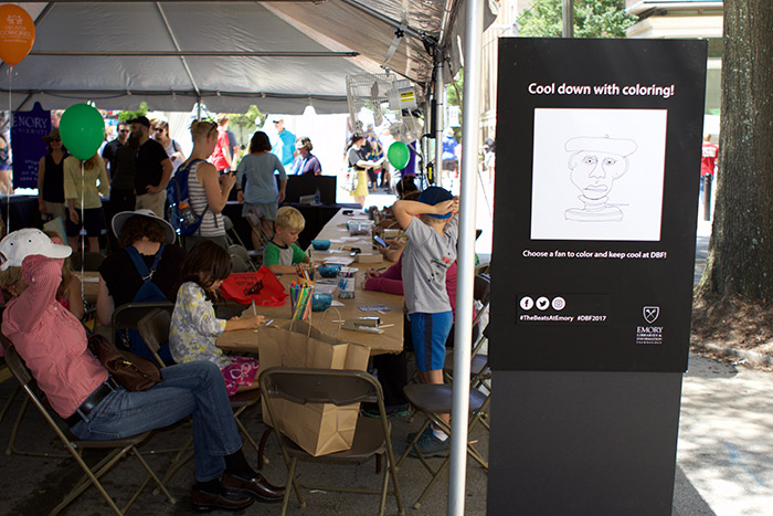 A group of children color at the Emory tent.