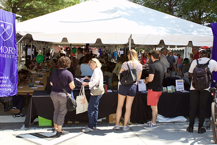Five individuals visit Emory's tent in downtown Decatur.
