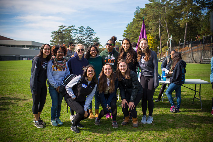 A group of students pose in front of a volunteer table at Emory Cares International Day of Service.