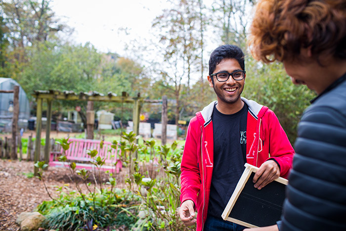 Two students share a smile as they work at the community gardens.