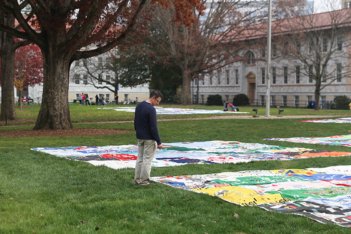 An adult male stands in front of a quilt, reading the names.