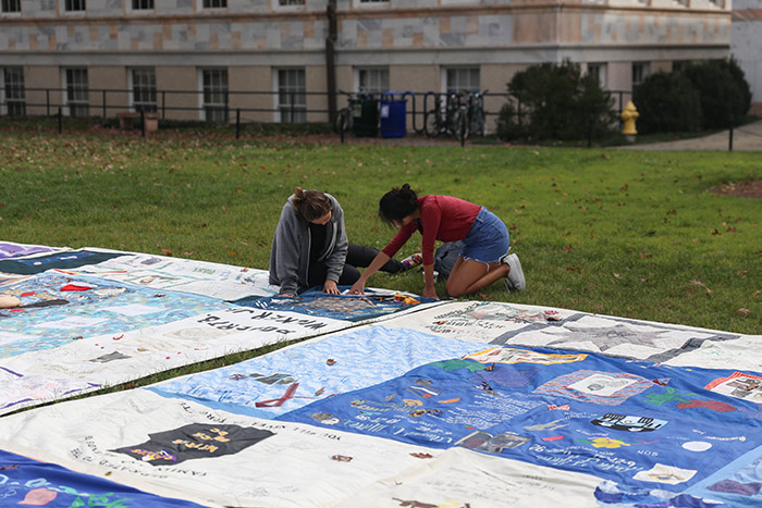 Two female students kneel next to a quilt, and one points to a panel.
