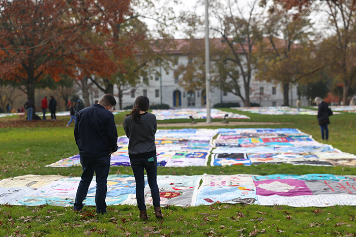 Two students stand in front of a quilt, reading the names.