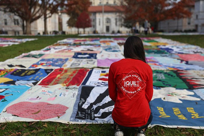 A young woman wearing a t-shirt from the event, kneels in front of a quilt.