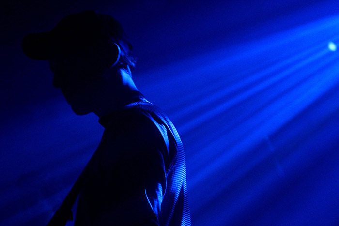 A member of the group stands in the dark blue hue of stage lighting.