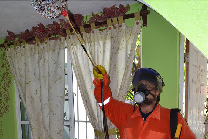A research technician donning PPE sprays the ceiling of a home in Merida, Mexico.