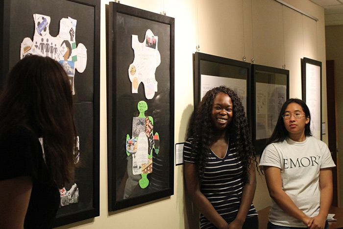 Students look at art in the class gallery.