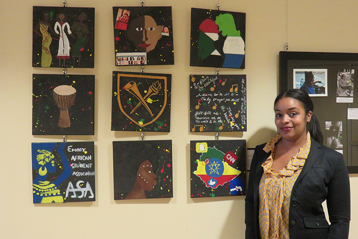 Professor Nicole Morris stands next to student art.