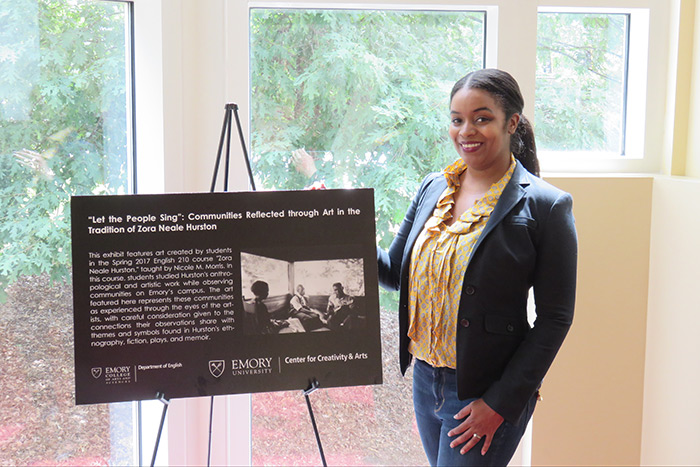 Professor Nicole Morris stands next to a sign at the opening of her class's exhibit.