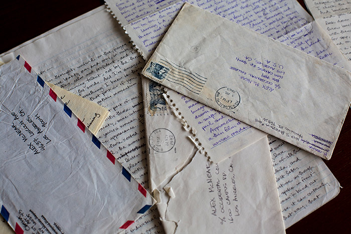 Several other letters and their envelopes sit, fanned out on a table.