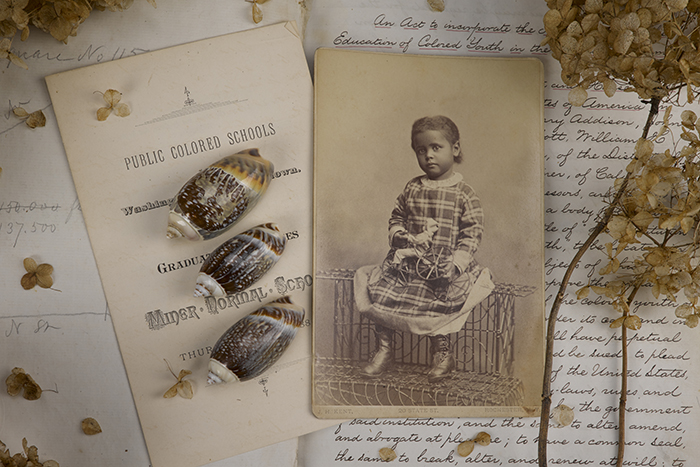 "A photo of one of the vignettes includes a collage of handwritten class notes, a ""Public Colored Schools"" document and a photo of small girl."