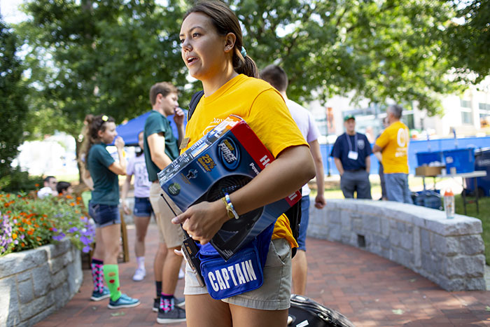 A student volunteer carries various items into a dormitory to help a student move in