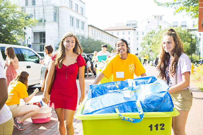 A student volunteer in a yellow t-shirt helps two students move in by rolling items in a large cart