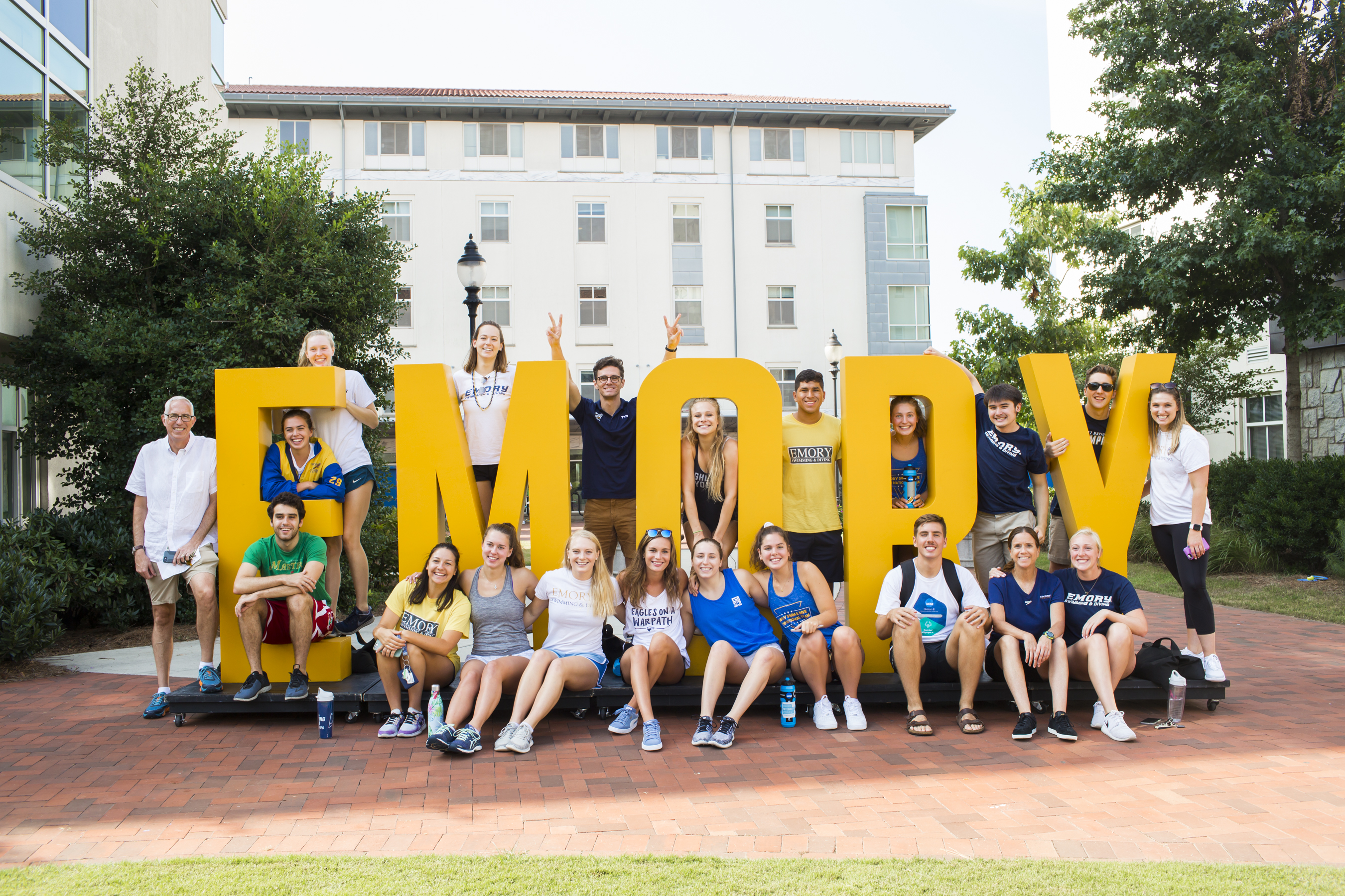 Several students and parents pose around a sculpture that says the word Emory