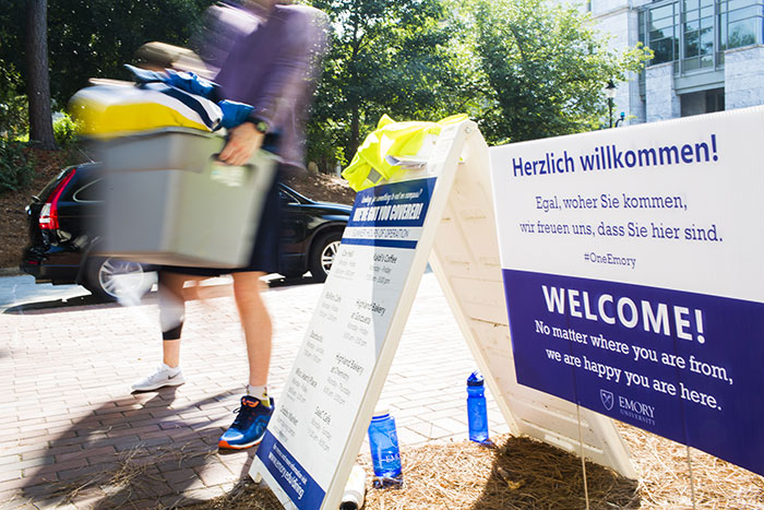 Students walk past welcome signs, carrying bins