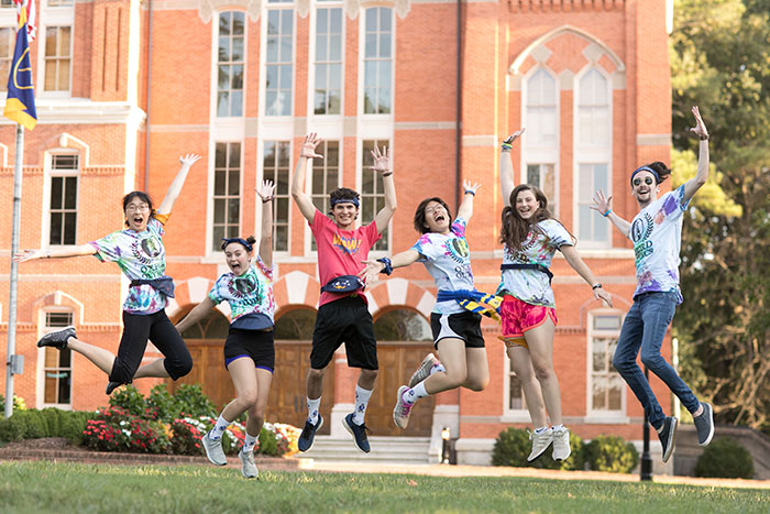 Students wearing various Oxford Olympics t-shirts jump synchronously in the quad