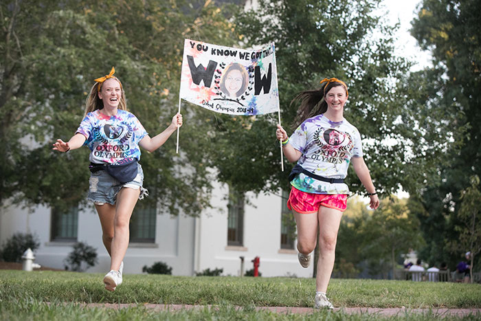Two students run through the quad carrying a sign for the team