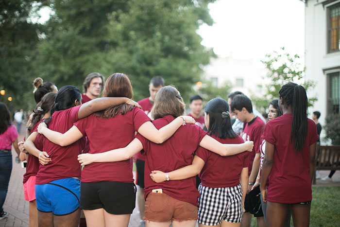 Students wearing maroon t-shirts wrap their arms around each other in a huddle