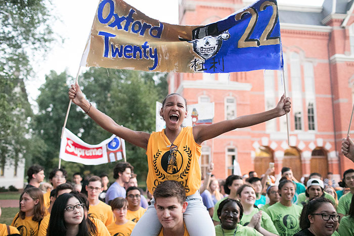 A student wearing an Emory gold t-shirt carries a banner while riding on the shoulders of another classmate