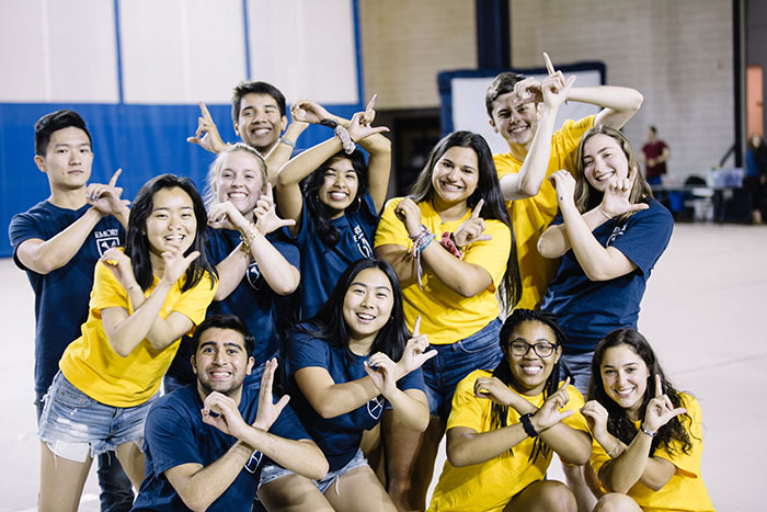 Students dressed in Emory colors pose before their Songfest performance