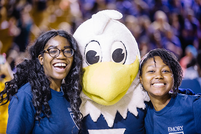 Two students pose with Swoop, Emory's athletics mascot