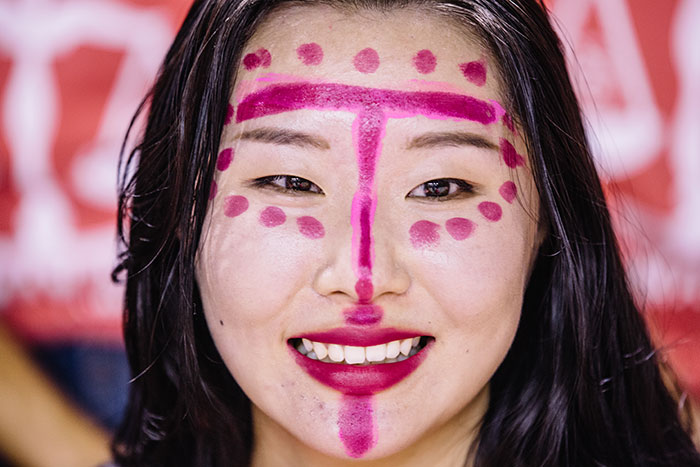 A student dons fuchsia face paint