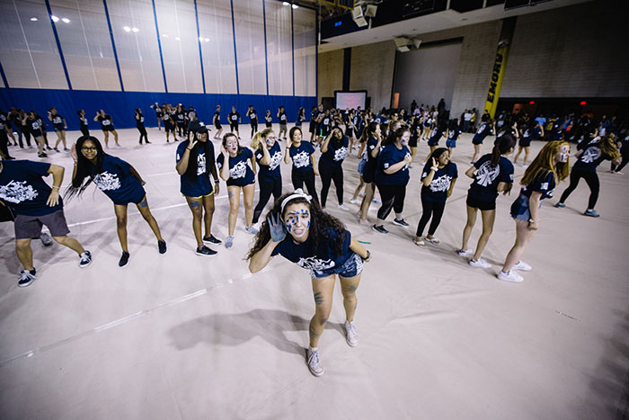 Students perform at Songfest, striking poses and making formations