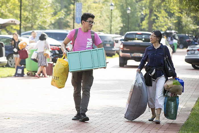 Student volunteers help students move in by rolling their belongs into the dorms