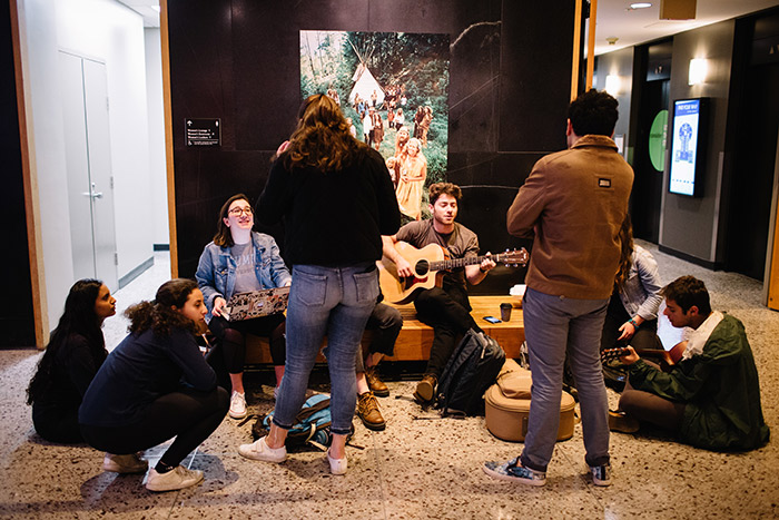 Emory students play guitar and chat in the Rose Library