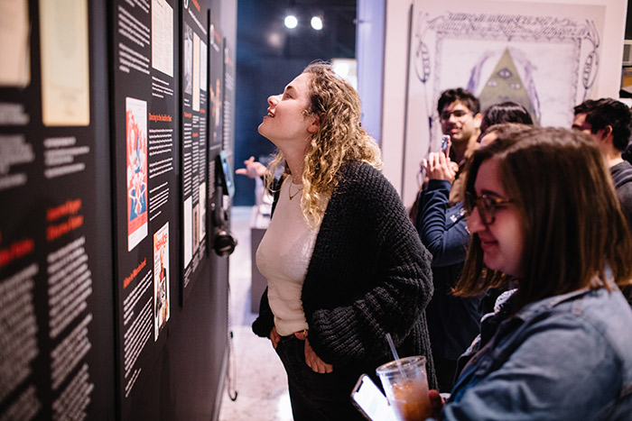 Two young women and several other students in the background read exhibit information hung on the wall