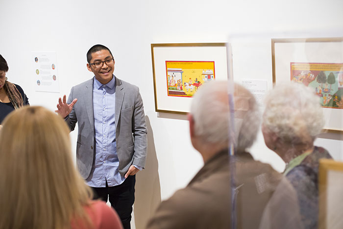 A young man speaks to a crowd about a particular work of art on display