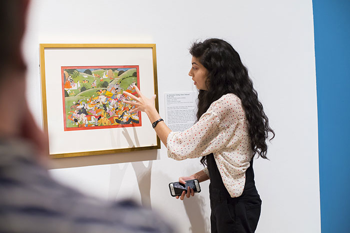 A student points at details in a work of art on display