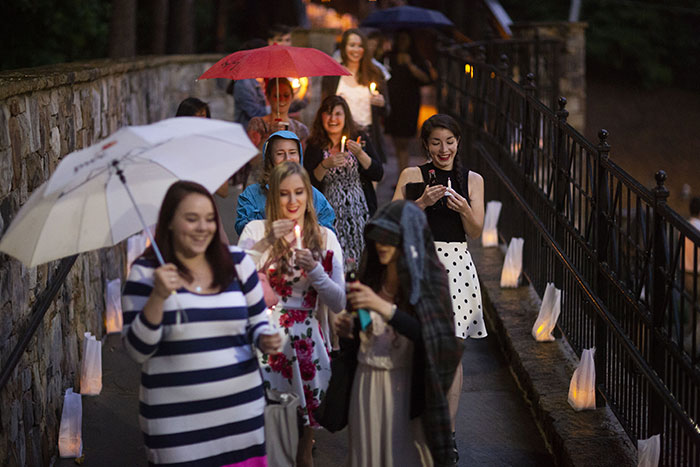 A large group of students walk across the bridge over Houston Mill Road carrying umbrellas and candles for the Candlelight Crossover